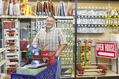 一个成熟人的画象有购物车的在五金店 库存照片