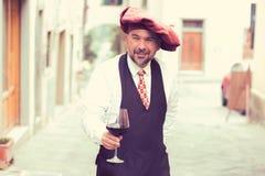 一个成熟愉快的人的画象有杯的红葡萄酒户外在老意大利村庄 免版税库存图片