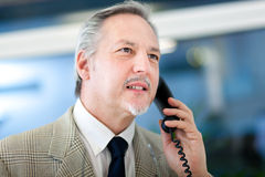一个成熟的商业人的画象讲话在电话 免版税库存图片
