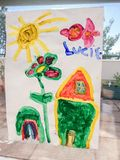一个房子和一个庭院的儿童的图画在太阳下 免版税库存照片