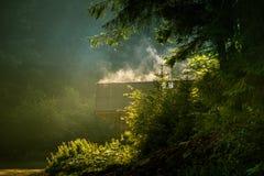 从一个房子屋顶的蒸发的湿气在罗马尼亚森林里 库存图片