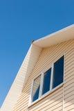 一个房子的屋顶顶层一个低角度视图自反对蓝天的白天 免版税库存图片