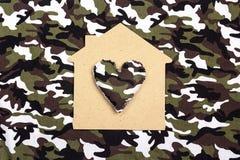 一个房子的标志有心脏的在伪装背景 免版税图库摄影