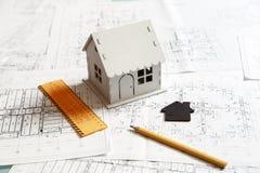 一个房子的模型在图纸和建筑师工具顶部的 图库摄影