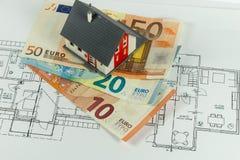 一个房子的模型金钱的和建筑计划 免版税库存图片