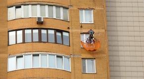 一个房子的门面的修理由工业登山人的 免版税库存图片
