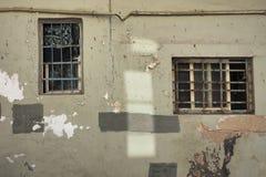 一个房子的难看的东西设计背景老墙壁有一个不对称的长方形箱子的有一个生锈的金属油漆格栅和补丁的  免版税库存图片