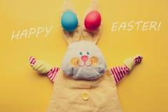 从一个手工制造玩具兔子和五颜六色的鸡蛋的复活节装饰在橙色背景 减速火箭的过滤器作用 库存照片