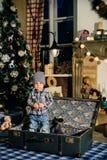 一个手提箱的小男孩在圣诞节装饰,孩子在新年 免版税库存图片