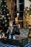 一个手提箱的小男孩在圣诞节装饰,孩子在新年 免版税库存照片