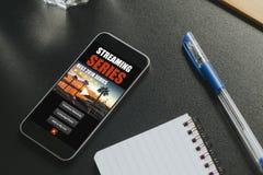 一个手机屏幕的电视系列节目网站app,安置在一张黑书桌 免版税库存图片