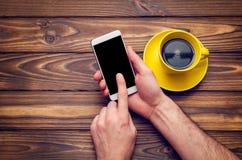 一个手机的大模型图象有一份空的黑屏幕和咖啡的在一张老木桌上的一个黄色杯子在咖啡馆 免版税库存图片