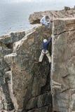 一个把柄的登山人感觉在水獭峭壁岩石面孔 免版税图库摄影