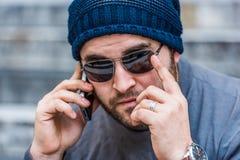 一个担心的人的画象有太阳镜的谈话在电话-看照相机 库存图片