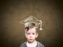 一个拉长的学生帽子的聪明的孩子 免版税图库摄影