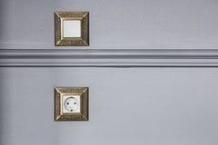 一个插口和一个开关在用长方形宝石装饰的墙壁上 免版税图库摄影