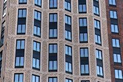 一个摩天大楼的五颜六色的砖墙有窗口的 库存图片