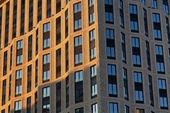 一个摩天大楼的砖墙有窗口的 太阳阐明的左边 图库摄影