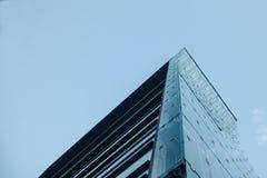 一个摩天大楼的角落在从底部看见的多云和冷的天空下 免版税图库摄影