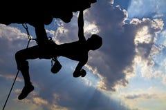 一个攀岩运动员的剪影岩石的 免版税库存图片