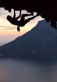 一个攀岩运动员的剪影日落的 免版税图库摄影