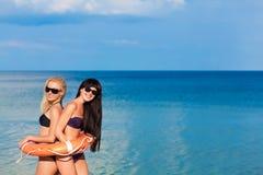 一个救生圈的美丽的女孩在海滩 图库摄影