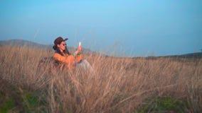 一个救生服、一个皮革牛仔帽和玻璃的一个女孩在草在电话坐并且做照片 股票录像