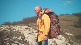 一个救生服、玻璃和一个大旅游背包的一个人在山站立,享受风景 影视素材