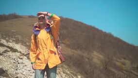 一个救生服、玻璃和一个大旅游背包的一个人在山站立 股票录像