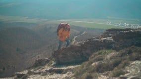 一个救生服、玻璃和一个大旅游背包的一个人沿土坎走,享受风景 股票录像