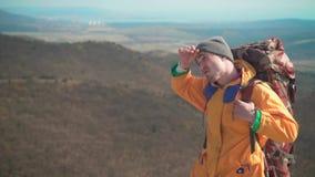 一个救生服、蓝色牛仔裤和一个帽子的一个人有一个大旅游背包的通过山和神色走开 股票录像