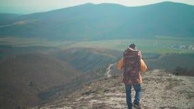 一个救生服、蓝色牛仔裤和一个帽子的一个人有一个大旅游背包的通过山和神色走开 影视素材
