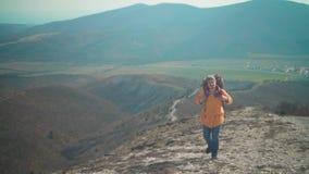 一个救生服、蓝色牛仔裤和一个帽子的一个人有一个大旅游背包的通过山和神色走开 股票视频
