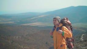 一个救生服、蓝色牛仔裤和一个帽子的一年轻人有一个大旅游背包的在山站立并且看  股票视频