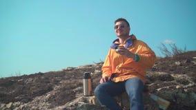 一个救生服、蓝色牛仔裤和玻璃的一个人在山坐,享受风景,喝从热水瓶的茶 股票视频