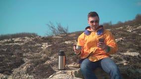 一个救生服、蓝色牛仔裤和玻璃的一个人在山坐,享受风景,喝从热水瓶的茶 股票录像