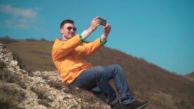一个救生服、蓝色牛仔裤和玻璃的一个人在山坐,享受风景,拍摄在电话的录影 影视素材