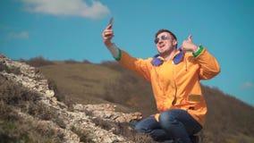 一个救生服、蓝色牛仔裤和玻璃的一个人在山坐,享受风景,采取selfie,照片 股票录像