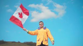 一个救生服、蓝色牛仔裤和玻璃的一个人在山站立并且从一边到另一边挥动加拿大的旗子 股票视频