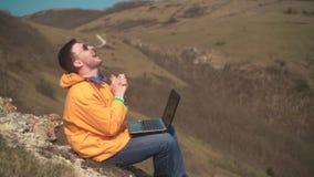 一个救生服、蓝色牛仔裤和玻璃的一个人在山,在膝上型计算机的工作坐并且高兴,喜悦的情感 影视素材
