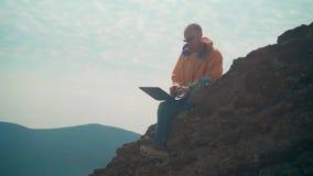 一个救生服、蓝色牛仔裤和玻璃的一个人坐在峭壁边缘并且研究膝上型计算机 股票视频