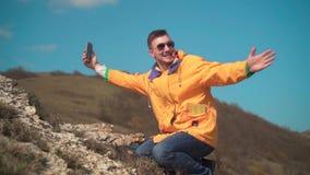 一个救生服、蓝色牛仔裤和玻璃的一年轻人在山坐,享受风景,谈话在录影 股票录像