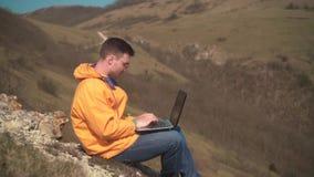 一个救生服、蓝色牛仔裤和玻璃的一年轻人在山坐,打开膝上型计算机并且开始工作 股票视频