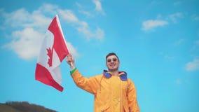 一个救生服、蓝色牛仔裤和玻璃的一年轻人在山站立,拿着加拿大的旗子 股票视频