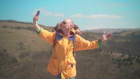 一个救生服和玻璃的一个人在山在录影站立,享受风景并且谈话 影视素材