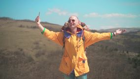 一个救生服和玻璃的一个人在山在电话站立,享受风景并且做照片 股票视频