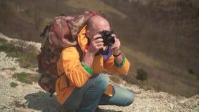 一个救生服和玻璃的一个人在山在dslr照相机站立,享受风景并且做照片 股票录像