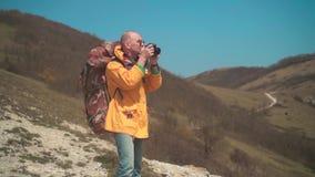 一个救生服和玻璃的一个人在山在dslr照相机站立,享受风景并且做照片 股票视频