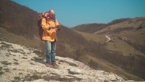 一个救生服和玻璃的一个人在山站立,享受风景和是由地图引导的 影视素材