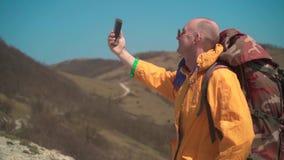 一个救生服和玻璃的一个人在山站立,享受风景并且做selfies 股票录像